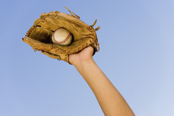 Baseball player catching ball in baseball glove, close-up of hand in glove