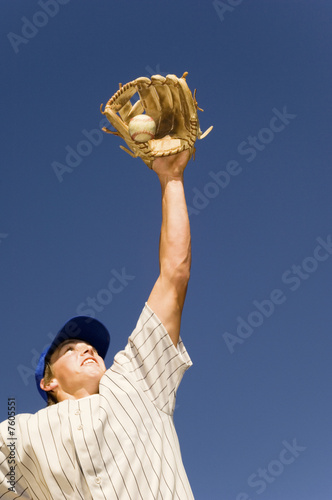 Baseball player catching ball in baseball glove, low angle view