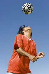 Soccer player heading ball, portrait
