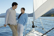 Young couple standing on bow of sailboat