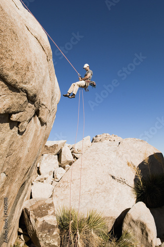 Man Rappelling on Cliff