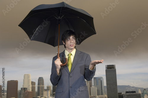 Business man checking for rain under umbrella in city
