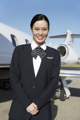 Stewardess in uniform, standing Beside a private jet