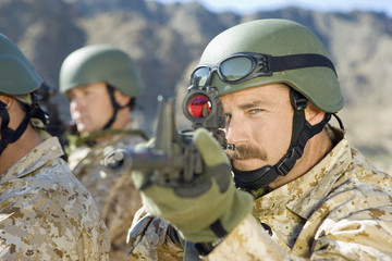 Soldier aiming rifle, outdoors, close-up