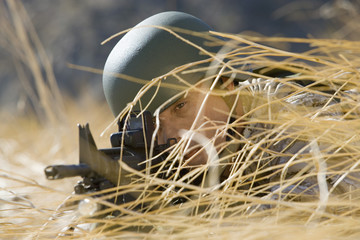 Soldier aiming rifle, hiding in long grass, close-up
