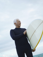Senior man carrying surfboard, low angle view