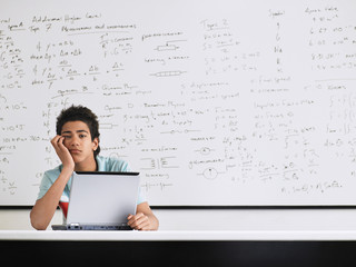 Teenage boy looking bored in front of whiteboard in classroom