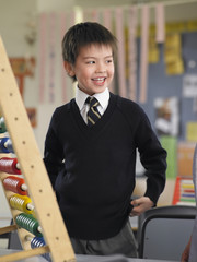 Elementary schoolboy standing by abacus in classroom