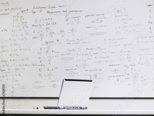 Laptop in front of whiteboard in classroom