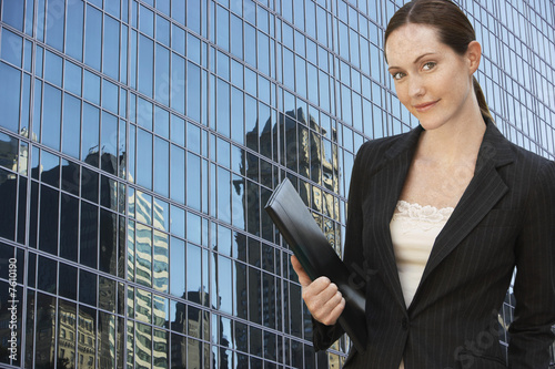 Businesswoman holding portfolio outside office building, portrait