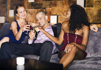 One Man and Two Women Lounging at Bar