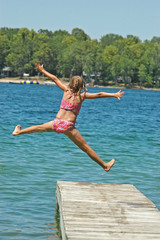 Young Girl Jumps Off Dock into Lake Extending Arms and Legs