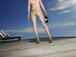 Woman in a Bathing Suit Holding a Bottle of Champagne
