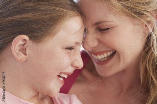 Girl with mother laughing, head and shoulders