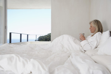 Woman Enjoying a Beverage in Bed