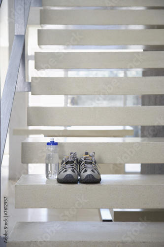Pair of athletic shoes and water bottle on stairs