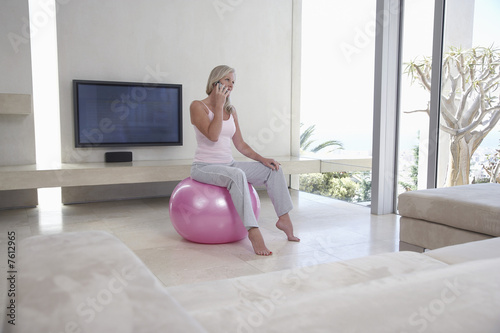 Woman Telephoning on Exercise Ball