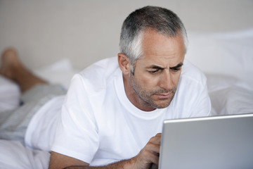 Man using laptop, lying on stomach on bed