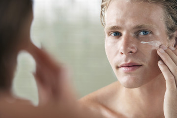 Man applying facial cream in front of mirror