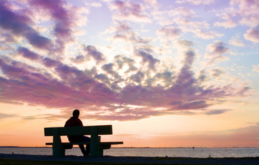 silhouette on man on bench watching sunset