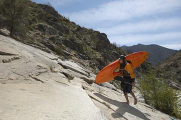 Female kayaker walking on rock, side view
