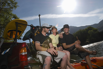 Three kayakers relaxing with beer
