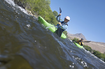 Two people kayaking in mountain river