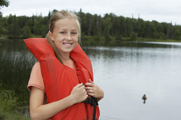 USA, Alaska, teenage girl wearing life jacket by lake, portrait