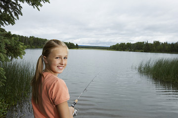 USA, Alaska, teenage girl fishing at lake, portrait