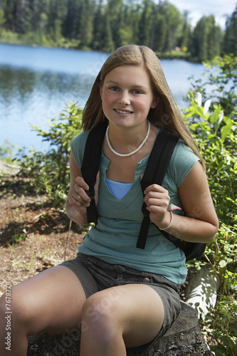 USA, Alaska, teenage girl wearing backpack at lake, portrait