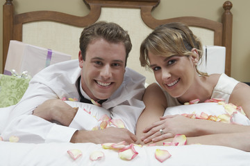 Bride and groom relaxing on bed among presents, portrait