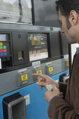Man pushing buttons on gas pump