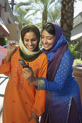 Two muslim women reading message in mobile phone