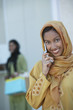 Two muslim woman, one talking on mobile phone