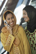 Two muslim woman, one talking on mobile