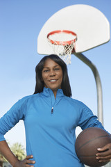 Senior woman on outdoor basketball court, portrait
