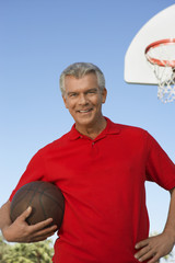 Senior man on outdoor basketball court, portrait