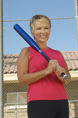 Senior woman with baseball bat outdoors, portrait