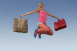 Portrait of young woman jumping with shopping bags in park