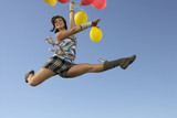 Young woman doing splits in air holding balloons