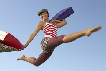 Portrait of young woman jumping with shopping bags