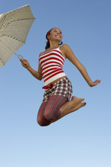 Young woman mid air with umbrella
