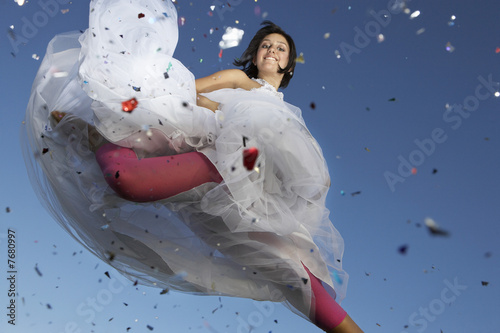 Portrait of young woman in wedding dress jumping