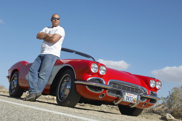 Man standing beside classic car on road