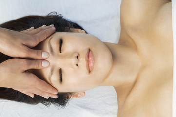 Young woman having head massage at health spa