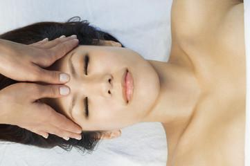 Young woman having head massage at health spa