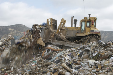 Digger moving waste at landfill site