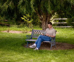 Man reading newspaper under tree