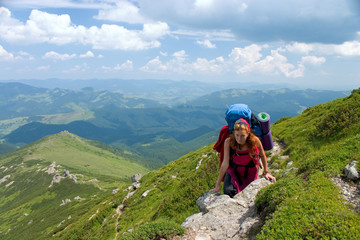 hiker girl with backpack in mountains