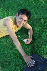 young man with laptop and music on green grass